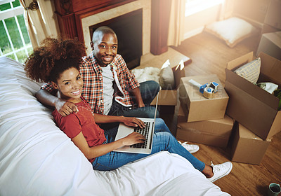 Buy stock photo Portrait of a young couple using a laptop while moving into their new home