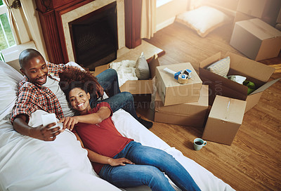 Buy stock photo Shot of a young couple taking a break while moving into their new home