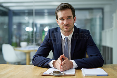 Buy stock photo Portrait of a confident young businessman sitting at a desk in an office