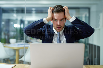Buy stock photo Shot of a stressed out businessman sitting in shock while working on a laptop in an office