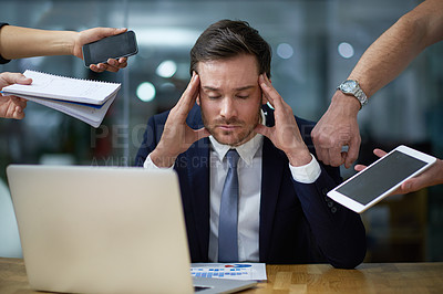 Buy stock photo Shot of a stressed out looking businessman surrounded by demanding colleagues while sitting at a desk in an office
