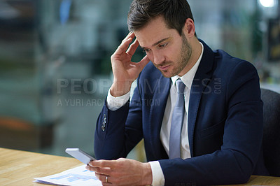 Buy stock photo Shot of a businessman using a cellphone while sitting at a desk in an office