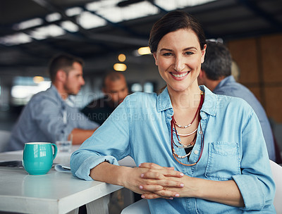 Buy stock photo Portrait of a smiling woman sitting at a table in an office with colleagues working in the background