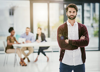 Buy stock photo Portrait of a young man standing in an office with colleagues meeting in the background