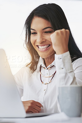 Buy stock photo Shot of a young businesswoman doing a fist pump while working on a laptop in an office
