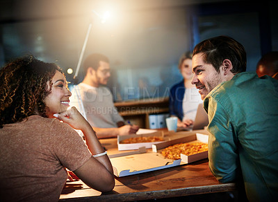 Buy stock photo Shot of a team of young businesspeople eating pizza while working late in the