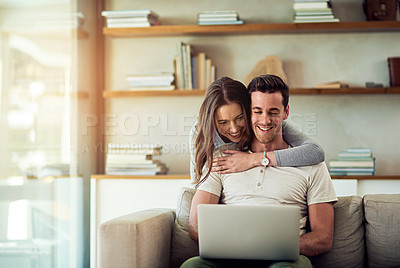 Buy stock photo Shot of a young woman hugging her husband while he uses a laptop on the sofa at home