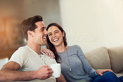 Buy stock photo Shot of a happy young couple relaxing together at home