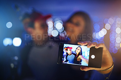 Buy stock photo Cropped shot of two friends taking a selfie while partying in a club
