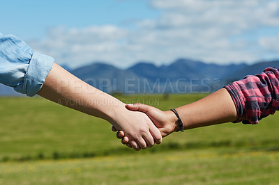 Buy stock photo Cropped shot of two unidentifiable people holding hands while standing in a grassy field
