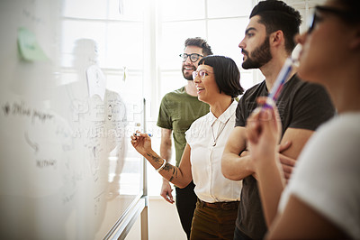 Buy stock photo Shot of a group of designers using a whiteboard to brainstorm in the office