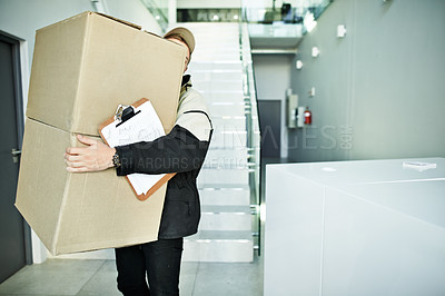 Buy stock photo Shot of an unidentifiable deliveryman carrying two large boxes
