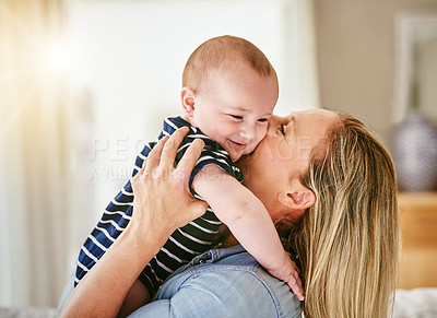 Buy stock photo Shot of a happy young mother playing with her baby boy at home