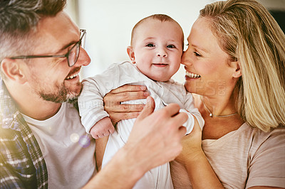 Buy stock photo Shot of two happy parents cuddling their baby at home