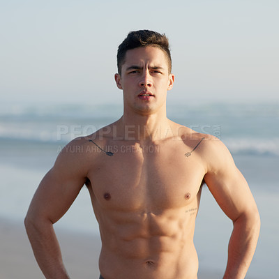 Buy stock photo Cropped portrait of a handsome young man standing with his hands on his hips at the beach