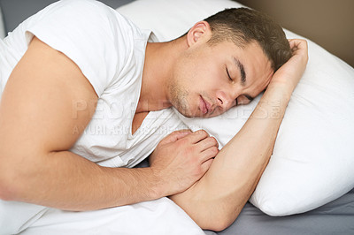 Buy stock photo Cropped shot of a handsome young man asleep in his bed
