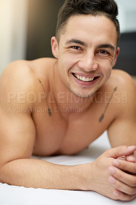 Buy stock photo Cropped shot of a handsome young man lying in bed