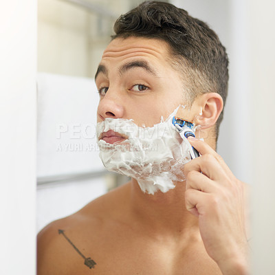 Buy stock photo Cropped shot of a young man shaving his beard