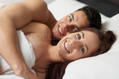 Buy stock photo Portrait of a happy young couple relaxing in bed together