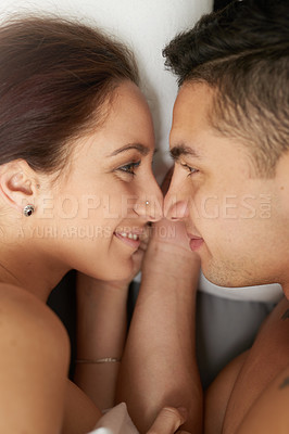 Buy stock photo Shot of a young couple sharing an intimate moment in bed