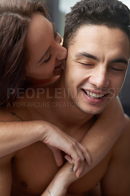 Buy stock photo Shot of a young woman lovingly kissing her boyfriend's ear