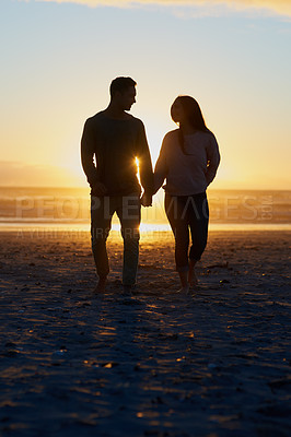 Buy stock photo Silhouette shot of a young couple on the beach