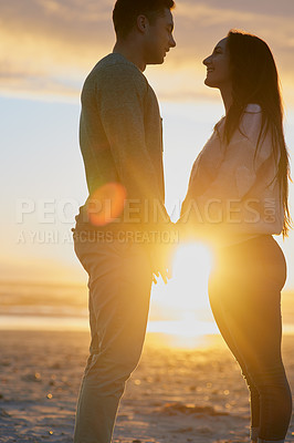 Buy stock photo Shot of a young couple at the beach at sunset