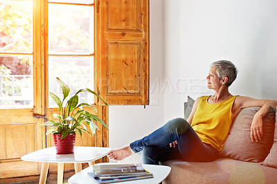 Buy stock photo Shot of a smiling mature woman relaxing on her sofa at home