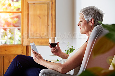 Buy stock photo Shot of a mature woman sitting in a chair at home relaxing with a digital tablet and a glass of wine