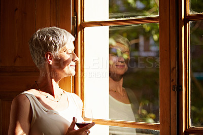 Buy stock photo Shot of a mature woman standing by a window at home drinking a glass of wine
