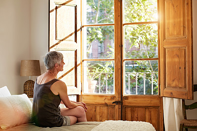 Buy stock photo Shot of a mature woman relaxing on a sofa by a window at home