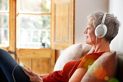 Buy stock photo Shot of a mature woman sitting on her sofa listening to music on a digital tablet
