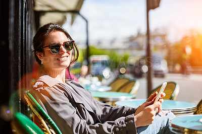 Buy stock photo Portrait of a smiling young woman sitting at a sidewalk cafe in Paris using a digital tablet
