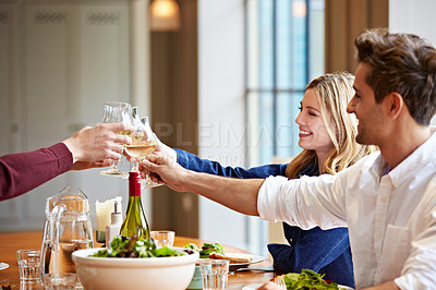Buy stock photo Shot of a group of friends toasting while enjoying a home-cooked dinner together