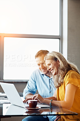Buy stock photo Shot of a mature couple sitting at their dining room table doing online banking using a laptop