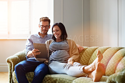 Buy stock photo Shot of a pregnant woman and her husband sitting on thier sofa using a digital tablet