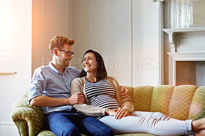 Buy stock photo Shot of a young expecting couple talking together while lying on the sofa at home