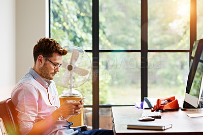 Buy stock photo Shot of a young man sending at text message while sitting in his home office