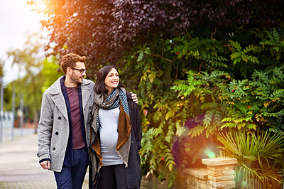 Buy stock photo Shot of a young pregnant woman and her husband enjoying a walk together