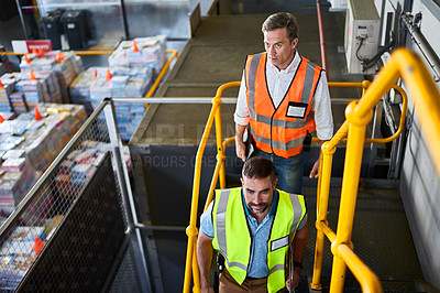 Buy stock photo Shot of two workers walking down stairs in a large warehouse