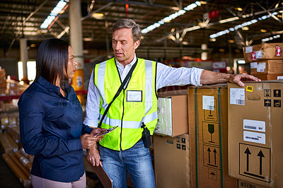 Buy stock photo Shot of two warehouse workers talking together while standing by boxes in a large warehouse