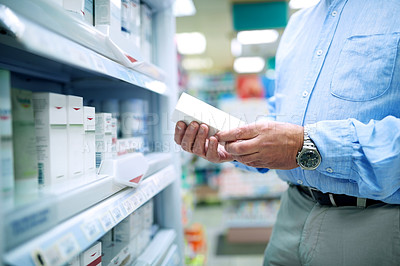 Buy stock photo Cropped shot of a man shopping for products at a pharmacy