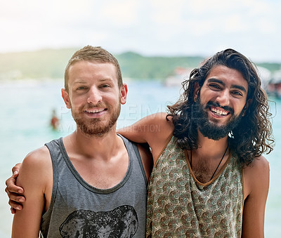 Buy stock photo Portrait of two male friends enjoying a day at the beach while on vacation