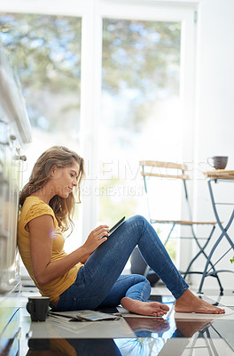 Buy stock photo Shot of an attractive young woman chilling on her kitchen floor using a digital tablet