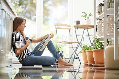 Buy stock photo Shot of an attractive young woman chilling on her kitchen floor reading a newspaper