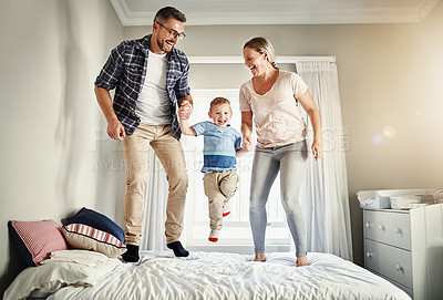 Buy stock photo Full length shot of a family of three jumping on a bed at home