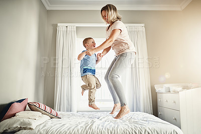 Buy stock photo Full length shot of a mother and son jumping on a bed at home