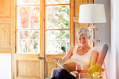 Buy stock photo Shot of a mature woman relaxing on her sofa at home reading a book