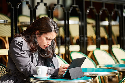 Buy stock photo Shot of a young woman sitting at a sidewalk cafe in Paris using a digital tablet