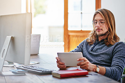 Buy stock photo Shot of a young man using a digital tablet while sitting at his desk in an office